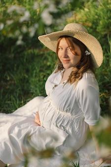Piękna młoda kobieta w ciąży w białej sukni w ogrodzie wiosną