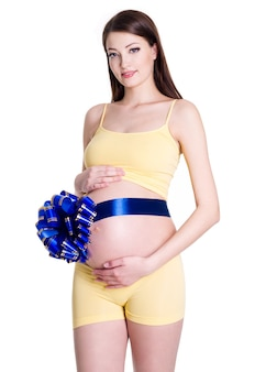 Piękna młoda kobieta w ciąży z obecną wstążką na brzuchu na białym tle