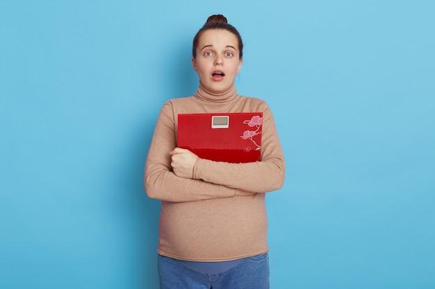 Piękna młoda kobieta w ciąży z zszokowanym wyrazem twarzy i ustami otworzył, trzymając w rękach czerwoną łuskę