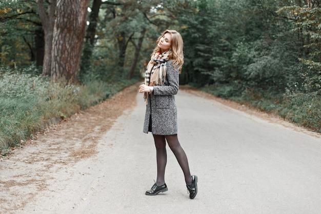 Piękna młoda kobieta w ciepły szalik i płaszcz vintage, spacery po drodze w parku.