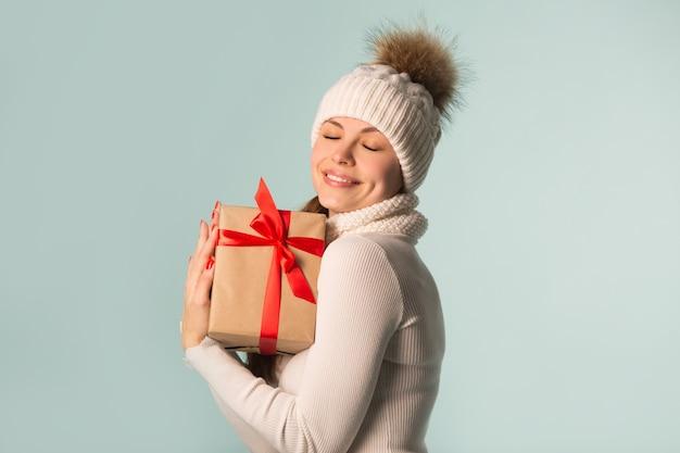 Piękna młoda kobieta w czapkę zimową z prezentem w ręku na niebieskim tle