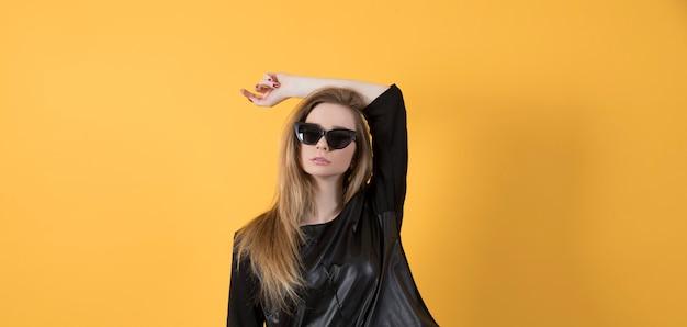 Piękna młoda kobieta w czarnej kurtce i czarnych okularach przeciwsłonecznych