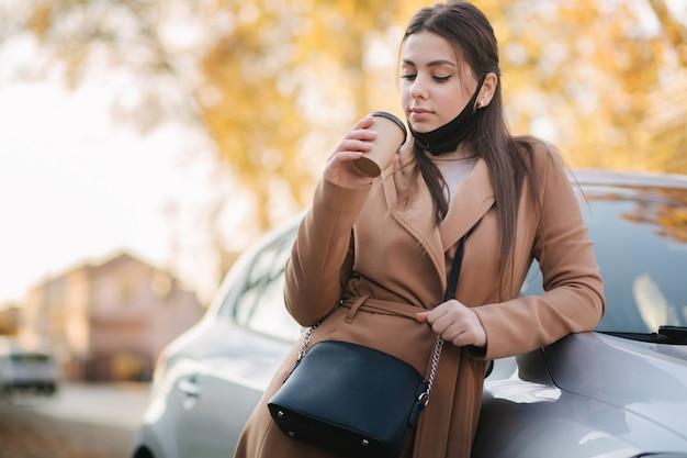 Piękna młoda kobieta w czarnej masce stoi przy samochodzie i pije kawę.