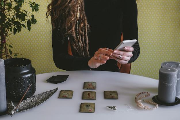 Piękna młoda kobieta w czarnej sztruksowej sukience zgaduje na kartach z runami