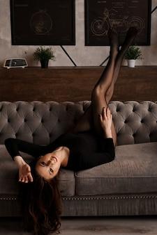 Piękna młoda kobieta w czarnych przezroczystych rajstopach na kanapie