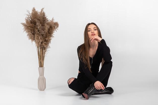 Piękna młoda kobieta w czarnych ubraniach pozowanie studio na szarej ścianie