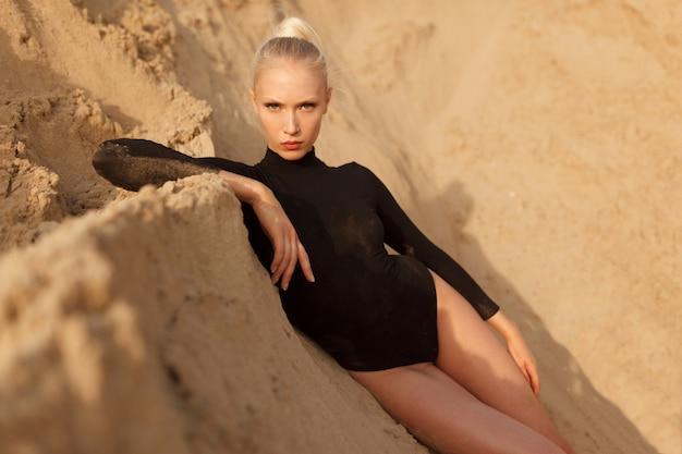 Piękna młoda kobieta w czarnym body leży na piasku ziemi. widok z przodu.