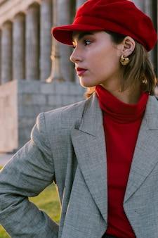 Piękna młoda kobieta w czerwonej czapce ze złotym kolczykiem w uszach patrząc od hotelu