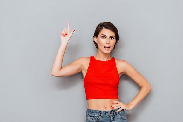 Piękna młoda kobieta w czerwonej górze wskazując palcem na szarym tle