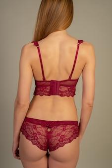 Piękna młoda kobieta w czerwonej koronkowej bieliźnie pozuje z plecami