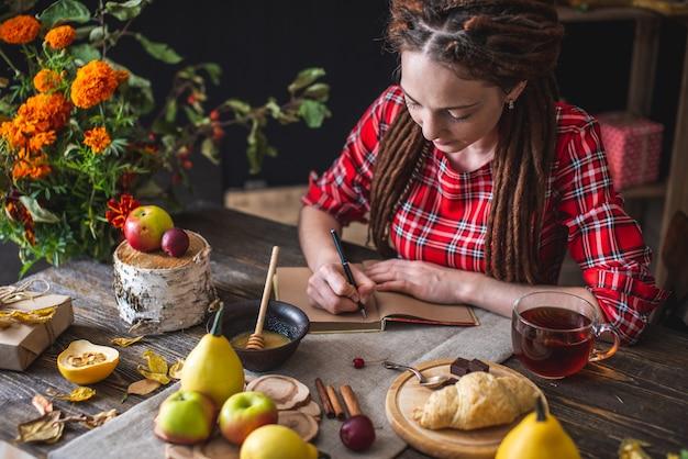 Piękna młoda kobieta w czerwonej sukience siedzi przy stole jesienią, pisząc w zeszycie