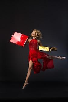 Piękna młoda kobieta w czerwonej sukience skoki w pozie baletowej na czarnym tle z pakietami