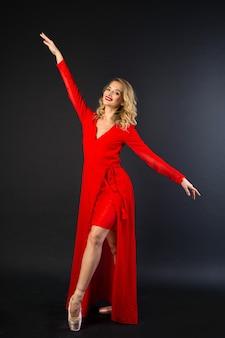 Piękna młoda kobieta w czerwonej sukience stoi w pozie baletowej na czarnym tle