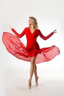 Piękna młoda kobieta w czerwonej sukience w baletowej pozie na białym tle