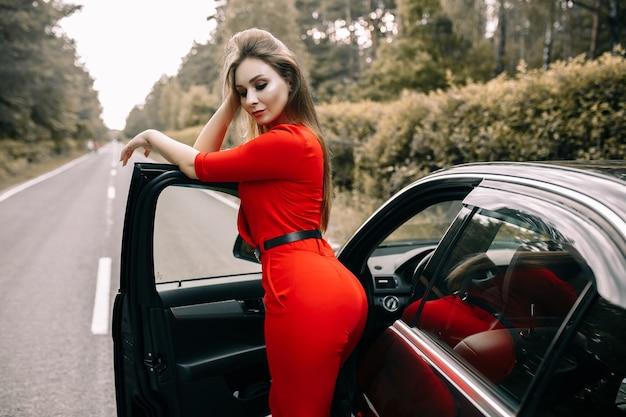 Piękna młoda kobieta w czerwonym kombinezonie stoi przy czarnym samochodzie na pustej drodze w lesie