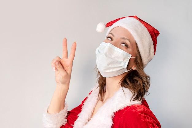 Piękna młoda kobieta w czerwonym stroju świętego mikołaja i masce ochronnej przed wirusem. koncepcja świętowania bożego narodzenia w pandemii covid 19 i kwarantannie. pani mikołajowa pokazuje gest palcem