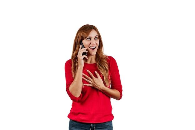 Piękna młoda kobieta w czerwonym swetrze, zaskoczona rozmową przez telefon, na białym tle na białej ścianie.