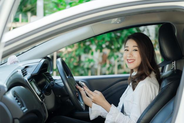 Piękna młoda kobieta w dobrym nastroju podróżuje samochodem.