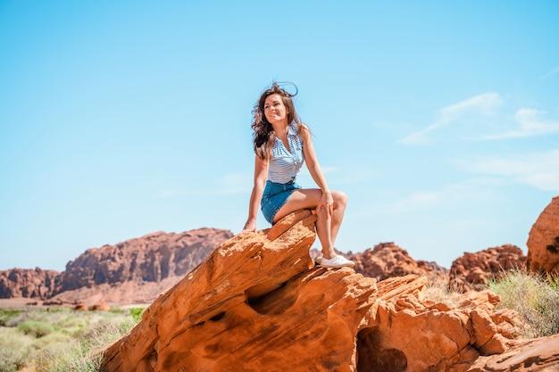 Piękna młoda kobieta w dolinie ognia w nevadzie z niesamowitym krajobrazem