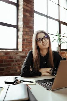 Piękna młoda kobieta w domowym biurze. praca z domu. koncepcja telepracy