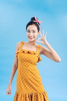 Piękna młoda kobieta w eleganckiej żółtej sukience koktajlowej w kropki wzór patrzy na aparat, śmiejąc się i pokazując znak ręką ok.