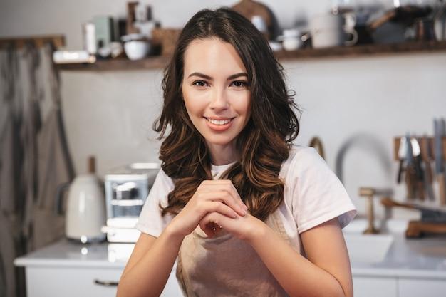 Piękna młoda kobieta w fartuchu siedzi w kuchni w domu
