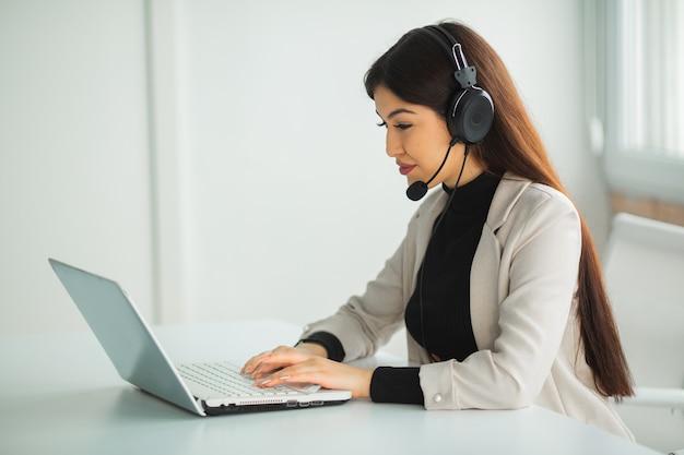 Piękna młoda kobieta w garniturze w biurze przy stole z laptopem w słuchawkach
