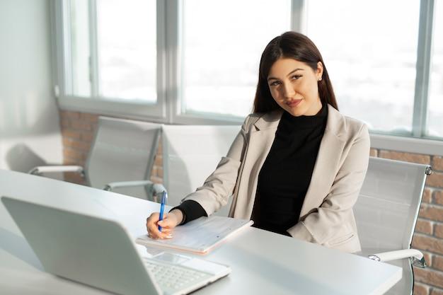 Piękna młoda kobieta w garniturze w biurze przy stole z laptopem