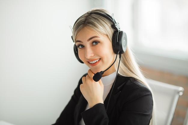 Piękna młoda kobieta w garniturze w biurze przy stole ze słuchawkami
