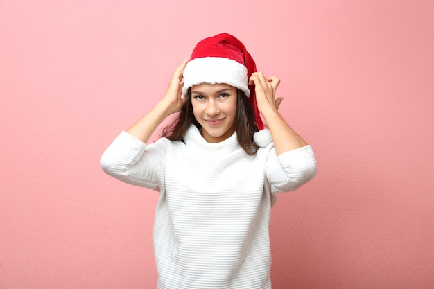 Piękna młoda kobieta w kapeluszu santa na różowej powierzchni