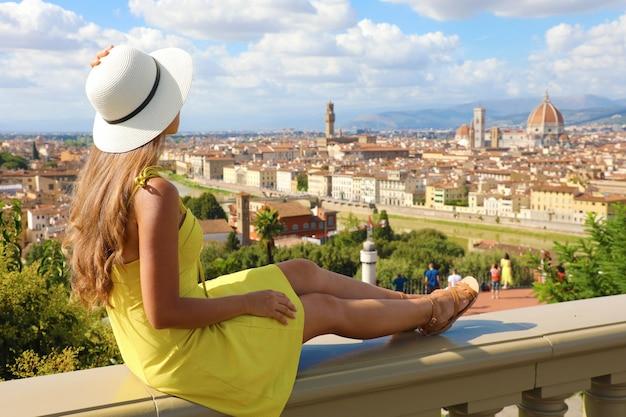 Piękna młoda kobieta w kapeluszu siedzi na ścianie, patrząc na wspaniały widok na florencję w toskanii we włoszech.