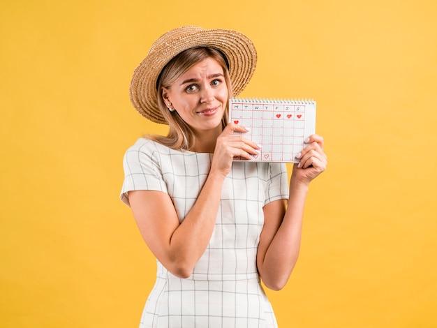 Piękna młoda kobieta w kapeluszu trzyma okres kalendarza