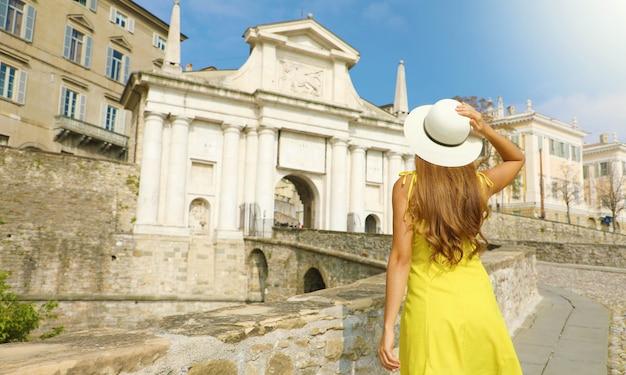 Piękna młoda kobieta w kapeluszu wspina się w kierunku bramy porta san giacomo w górnym mieście bergamo w słoneczny dzień. letnie wakacje we włoszech.