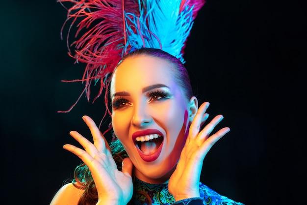 Piękna młoda kobieta w karnawale, stylowy kostium maskarady z piórami na czarnej ścianie w świetle neonu