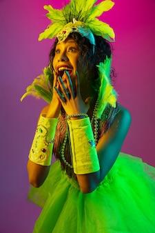 Piękna młoda kobieta w karnawale, stylowy kostium maskarady z piórami tańczącymi na gradientowym tle w neonie.