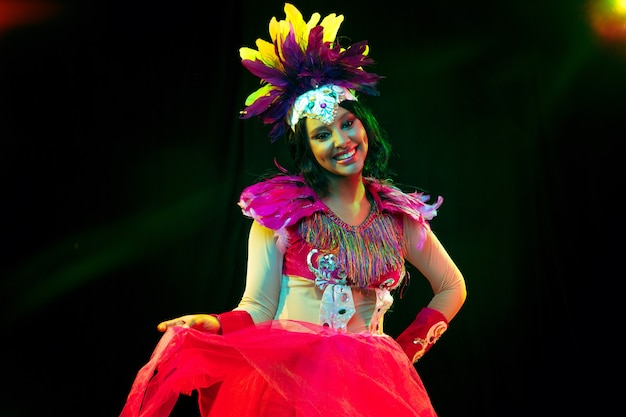 Piękna młoda kobieta w karnawałowej masce i stylowym kostiumie maskarady z piórami w kolorowych światłach i blaskiem na czarnej ścianie