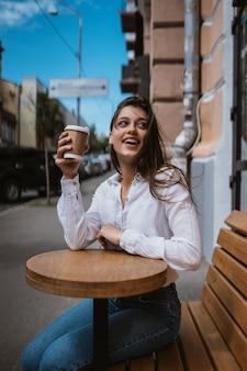 Piękna młoda kobieta w kawiarni ulicy pije kawę