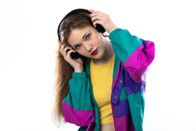 Piękna młoda kobieta w kolorowej kurtce i mienia hełmofonach