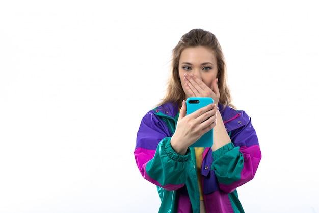 Piękna młoda kobieta w kolorowej kurtce i mienia smartphone