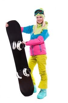 Piękna młoda kobieta w kombinezon narciarski i okulary narciarskie trzymać snowboard