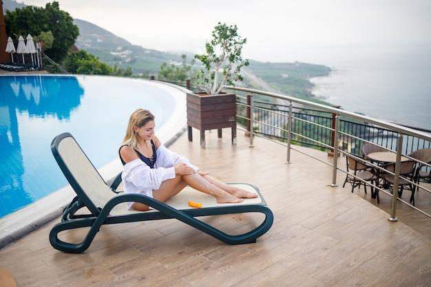 Piękna młoda kobieta w kostiumie kąpielowym i białej koszuli siedzi na leżaku przy basenie i smaruje swoje ciało kremem przeciwsłonecznym. letnia pielęgnacja skóry, ochrona przed poparzeniem skóry