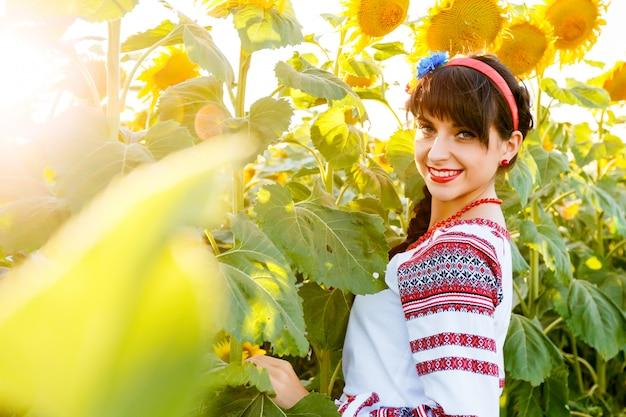 Piękna młoda kobieta w krajowej ukraińskiej bluzki embrodery patrzeje kamera na słonecznikowej roślinie przy zmierzchem