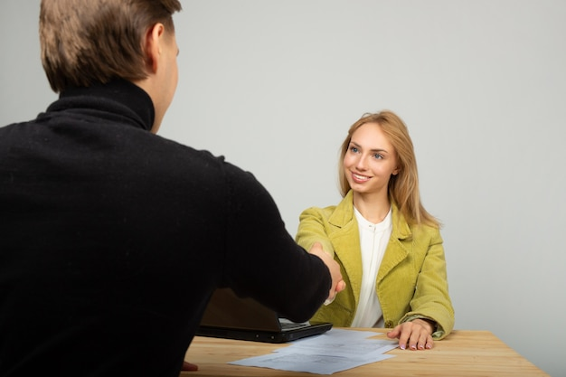 Piękna młoda kobieta w kurtce przy stole z laptopem z szefem