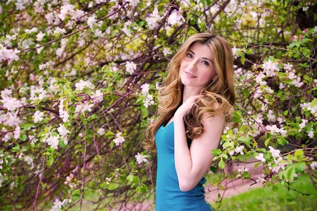 Piękna młoda kobieta w kwitnącym ogrodzie