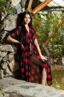 Piękna młoda kobieta w lekkiej sukience w kurorcie w tropikach