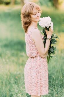 Piękna młoda kobieta w letniej sukience z piwoniami