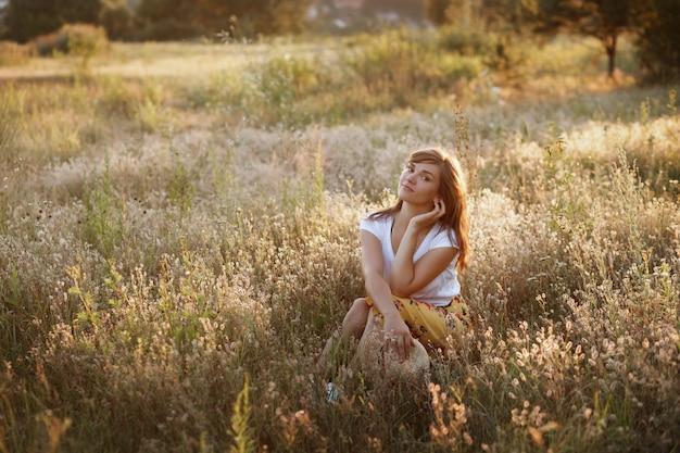 Piękna młoda kobieta w letnim polu