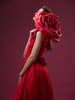 Piękna młoda kobieta w luksusowej sukience z różami, płatkami róż, stylowym wizerunkiem, czerwoną szminką