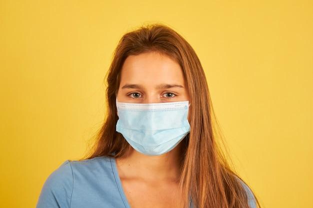 Piękna młoda kobieta w masce na twarz, aby zapobiec infekcji koronawirusem