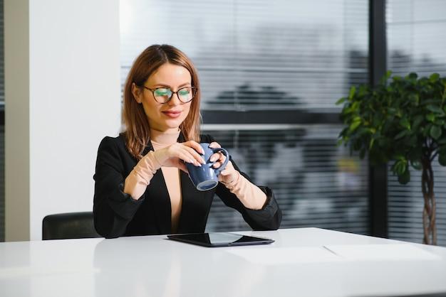 Piękna młoda kobieta w miejscu pracy za pomocą cyfrowego tabletu